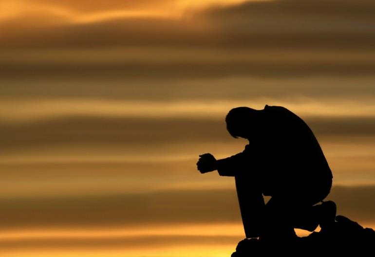 Homem ajoelhado rezando